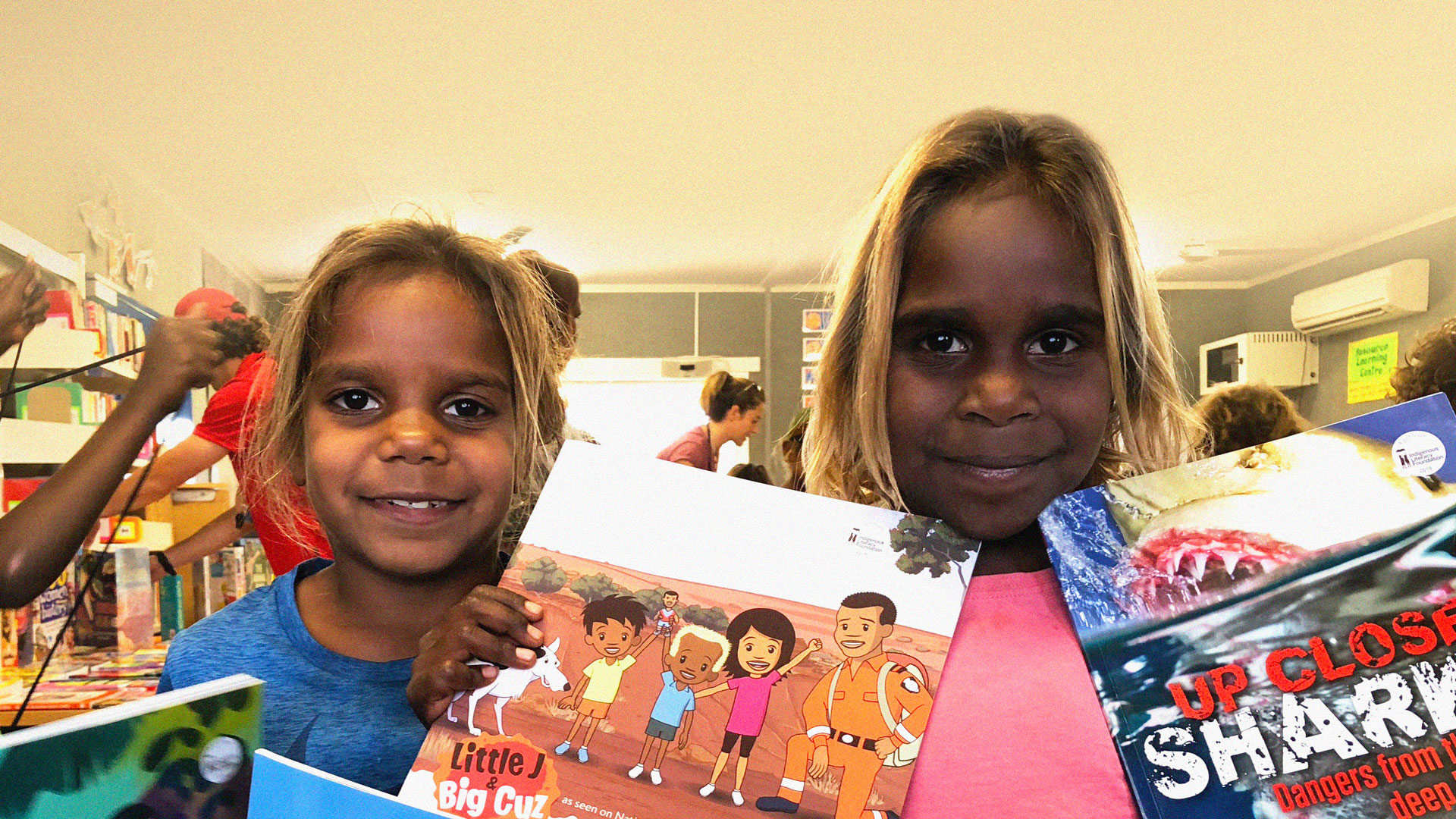 Two Indigenous Children with books from the Indigenous Literacy Foundation