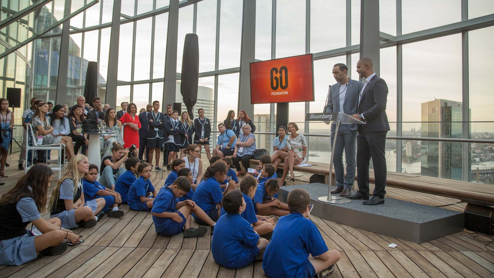 Adam Goodes and Michael O'Loughlin giving a speech for the GO Foundation to a class of students.